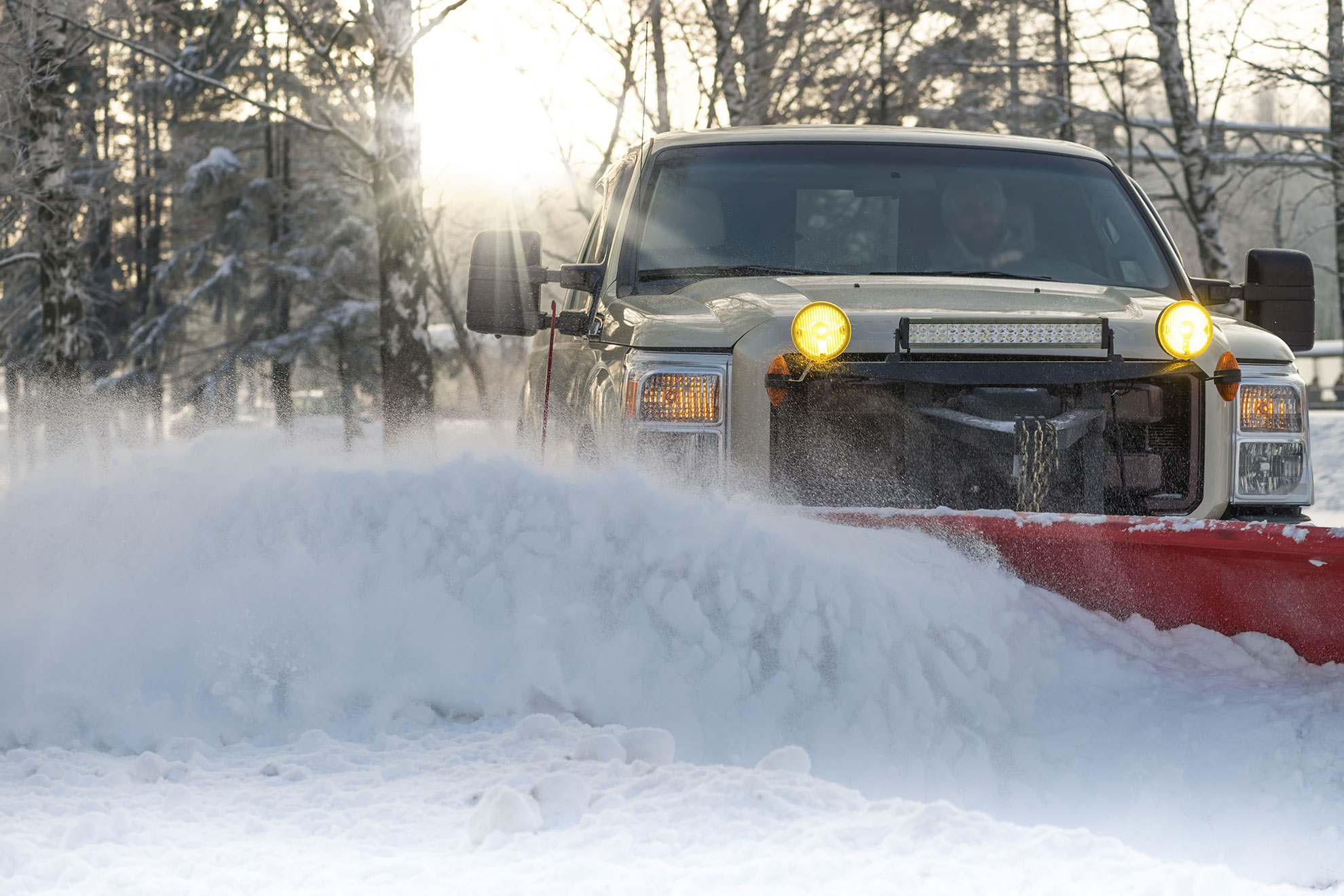 white pickup truck with red snowplow plowing snow